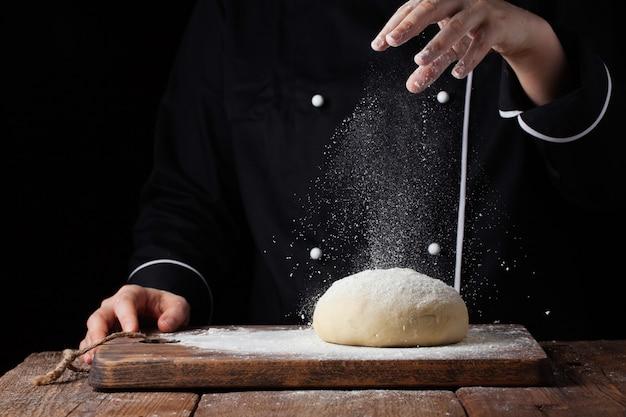 Chef mains verser la farine en poudre sur la pâte crue. Photo Premium