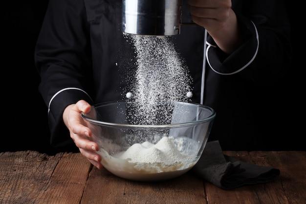 Chef mains verser la farine en poudre. Photo Premium