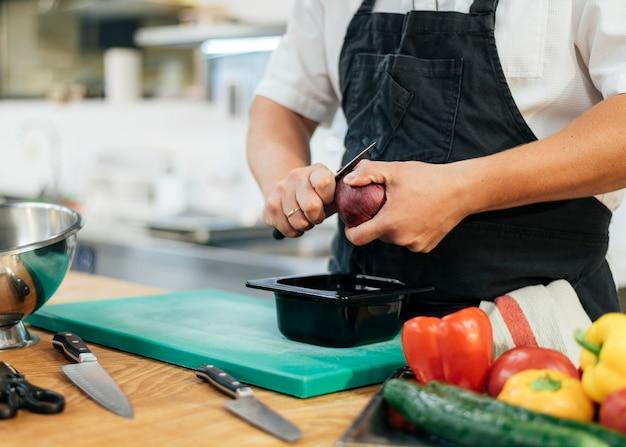 Chef Masculin Avec Tablier De Coupe De Légumes Photo Premium