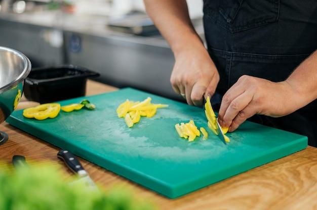 Chef Masculin Avec Tablier, Trancher Les Légumes Dans La Cuisine Photo Premium