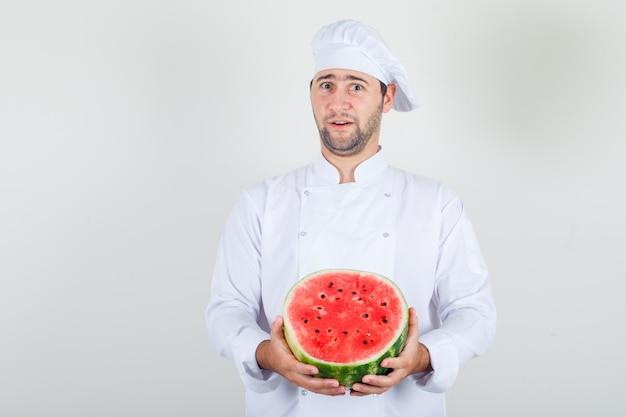 Chef Masculin Tenant La Pastèque En Tranches En Uniforme Blanc Et à La Recherche Positive. Photo gratuit