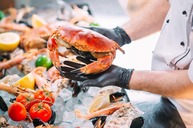 Le chef met les fruits de mer sur un plateau dans le restaurant. Photo Premium