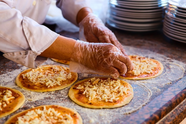 Chef Met Des Garnitures Sur Une Pizza Photo Premium