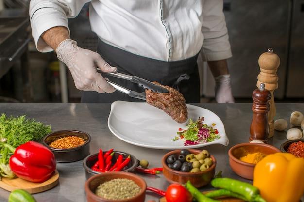 Chef mettant un steak grillé dans l'assiette avec une salade d'herbes Photo gratuit