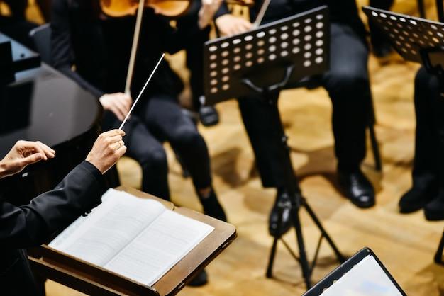 Chef d'orchestre par derrière dirigeant ses musiciens lors d'un concert. Photo Premium