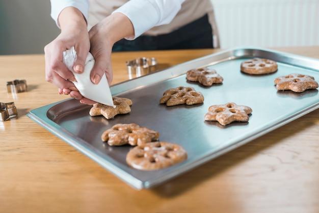 Chef pâtissier décorant de délicieux biscuits de différentes formes Photo gratuit