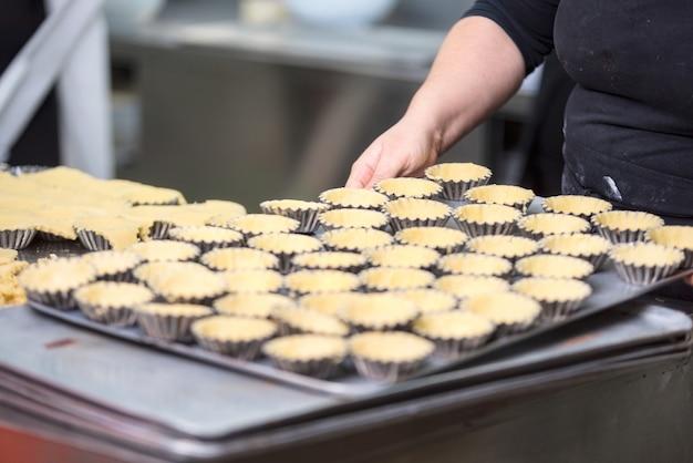Chef pâtissier préparant des tartelettes, mettant la pâte dans des plats allant au four, dans la cuisine de la pâtisserie. Photo Premium