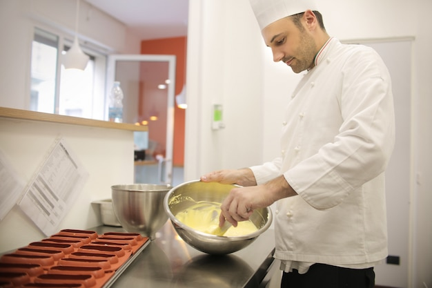 Chef pâtissier prépare la crème de gâteau Photo Premium