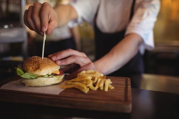 Chef Plaçant Cure-dent Sur Burger Au Poste De Commande Photo Premium