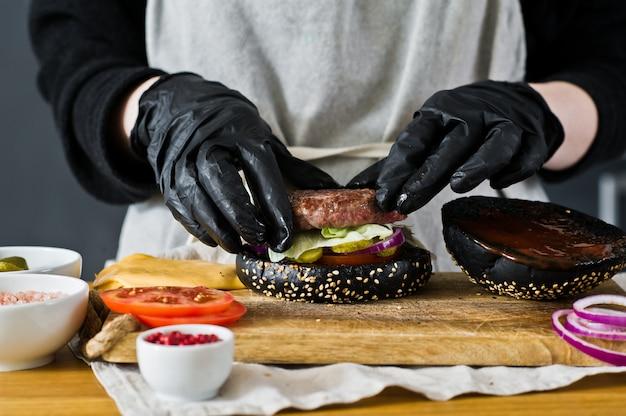 Le chef prépare un cheeseburger. le concept de la cuisson d'un burger noir. recette de hamburger fait maison. Photo Premium