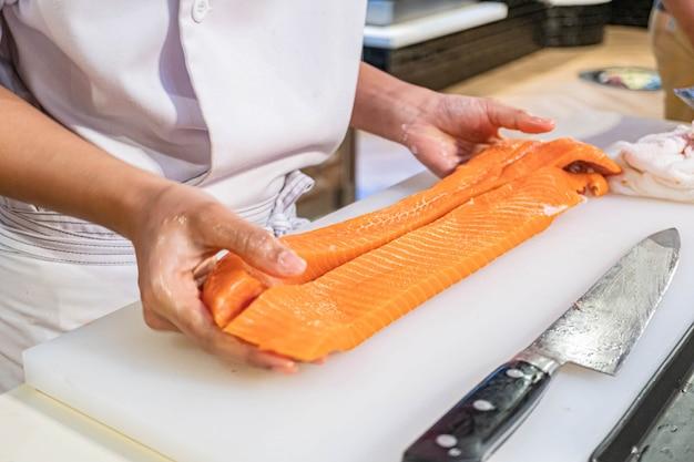 Chef prépare et coupe du saumon frais dans un restaurant japonais Photo Premium
