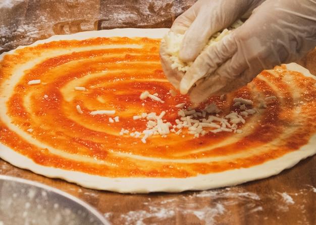 Le chef prépare de délicieuses pizzas dans la cuisine Photo Premium