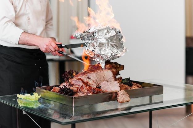 Chef Prépare La Dinde Au Four Sur Un Plateau Au Feu. Dinde Rôtie. Photo Premium