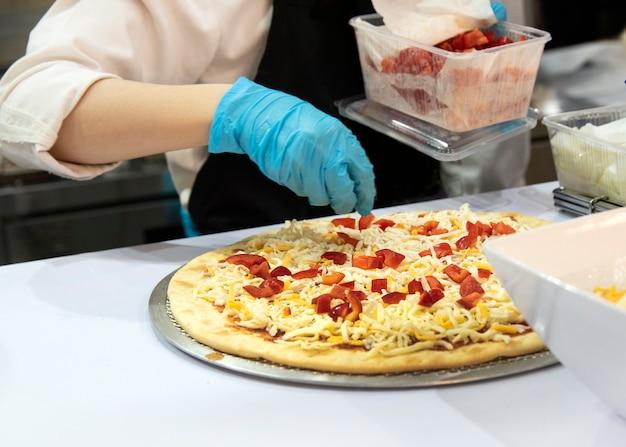Chef prépare une pizza, processus de fabrication de la pizza au restaurant de pizza Photo Premium