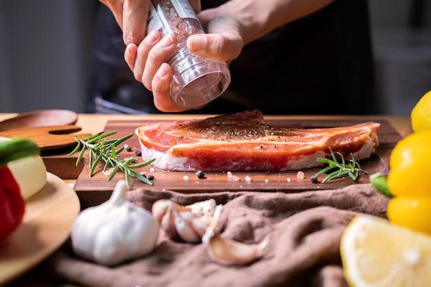 Le chef prépare un steak de porc avec sauce barbecue dans la cuisine Photo Premium