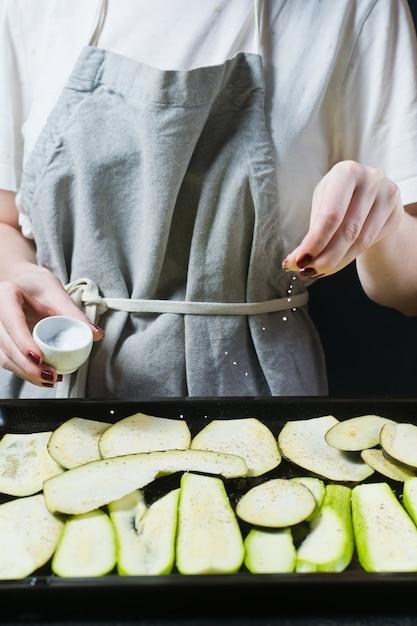Le chef saler les tranches d'aubergines. Photo Premium