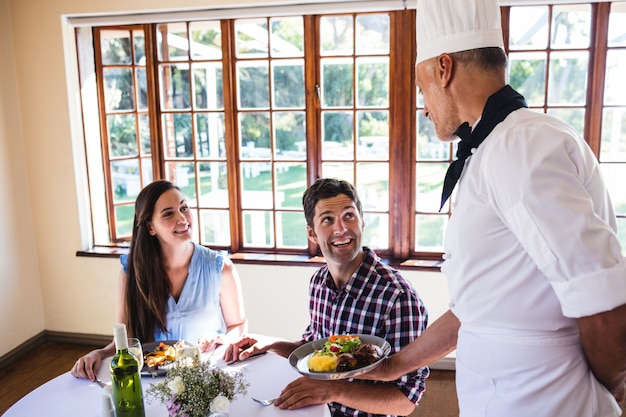 Chef servant une cuisine pour jeune couple assis dans un restaurant Photo Premium