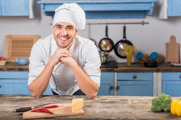 Chef souriant dans la cuisine Photo gratuit
