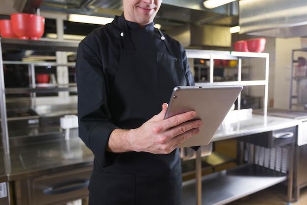 Chef avec une tablette Photo gratuit