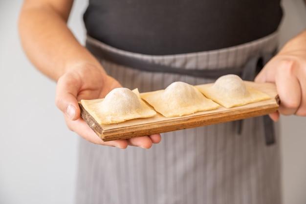 Chef tenant des pâtes farcies Photo gratuit
