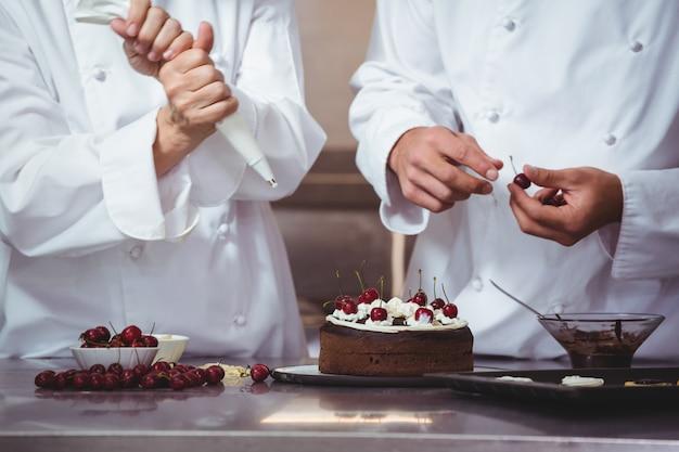 Chefs décorer un gâteau qu'ils viennent de faire Photo Premium