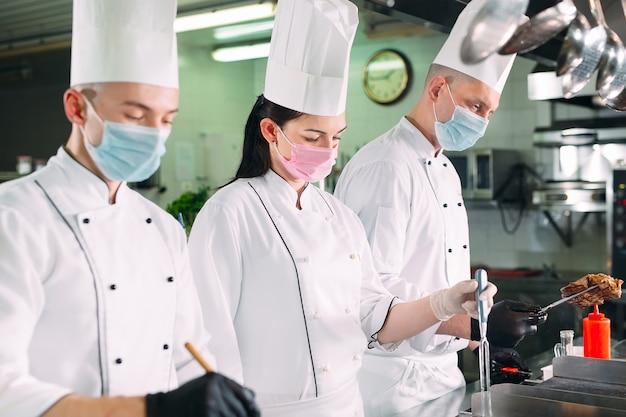 Des Chefs Portant Des Masques De Protection Et Des Gants Préparent La Nourriture Dans La Cuisine D'un Restaurant Ou D'un Hôtel. Photo Premium