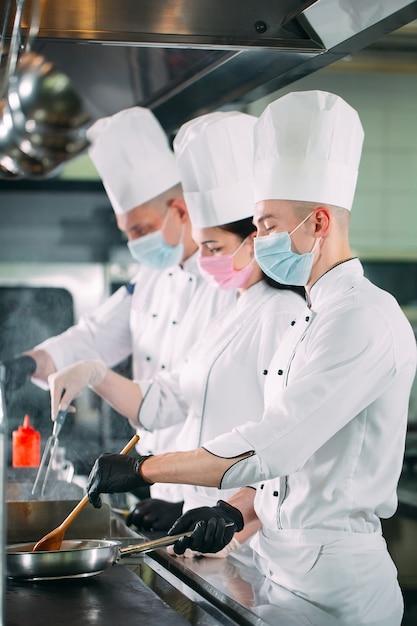 Les Chefs Portant Des Masques De Protection Et Des Gants Préparent La Nourriture Dans La Cuisine D'un Restaurant Ou D'un Hôtel. Photo Premium