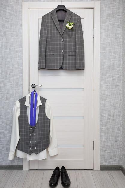 Une chemise blanche et une cravate violette, des chaussures noires sont suspendues à la porte Photo Premium