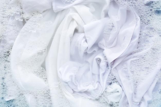 Chemise blanche imbibée de dissolution en poudre de détergent en poudre. concept de blanchisserie Photo Premium
