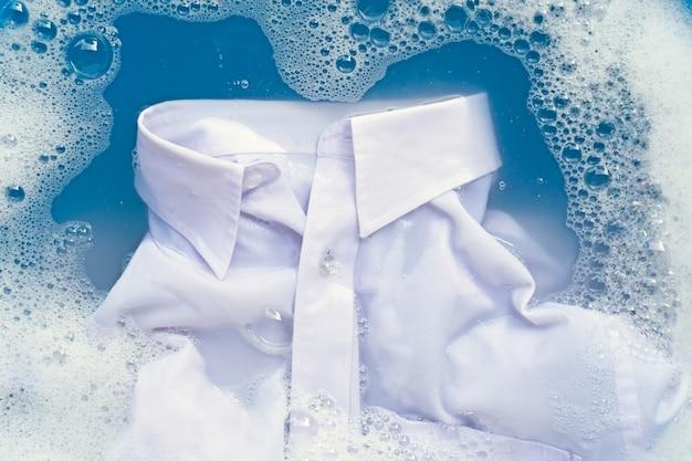 Chemise blanche trempée dans un détergent en poudre, dissolution dans l'eau Photo Premium