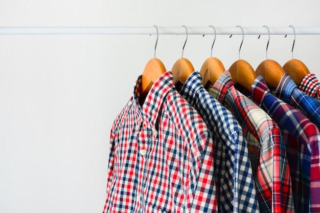 Chemise à carreaux à manches longues sur un cintre en bois accroché sur un panier à vêtements sur fond blanc Photo Premium