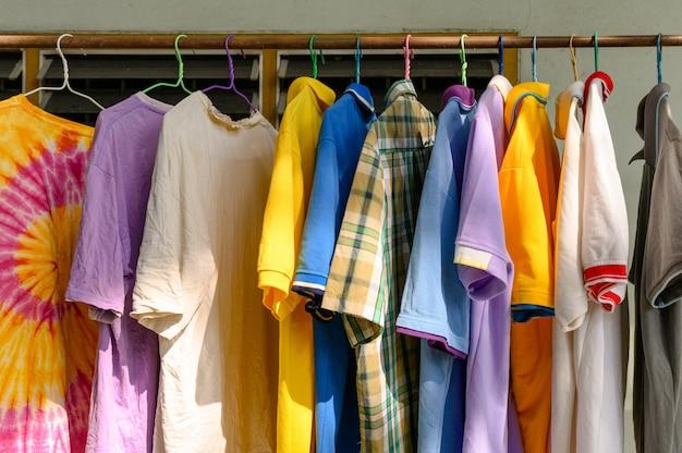 Chemise masculine colorée suspendu à une corde à linge sous le soleil Photo Premium