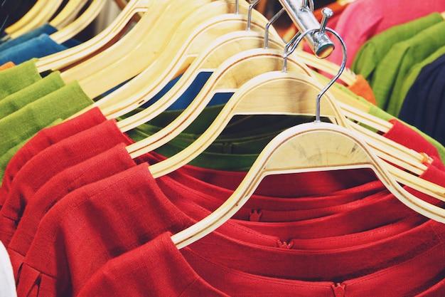 Chemises colorées suspendus sur une grille se bouchent Photo Premium