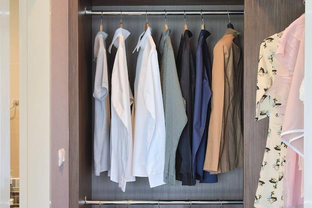 Les chemises de couleur classique sont suspendues dans une armoire en bois ouverte Photo Premium