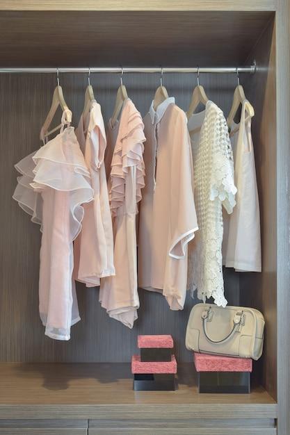 Les chemisiers en pastel sont suspendus dans une armoire en bois ouverte Photo Premium