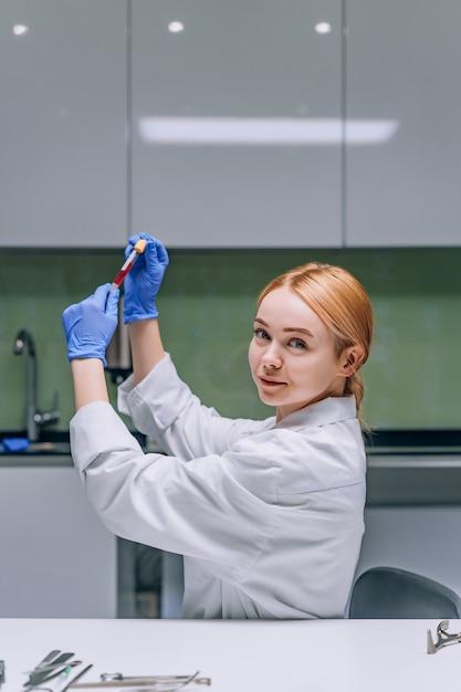 Chercheur Médical Ou Scientifique Féminin Regardant Un Tube à Essai Dans Un Laboratoire. Photo gratuit