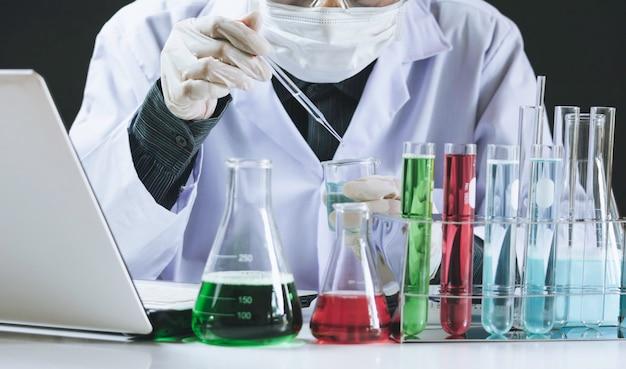 Chercheur avec tubes à essai chimiques de laboratoire en verre avec liquide Photo Premium