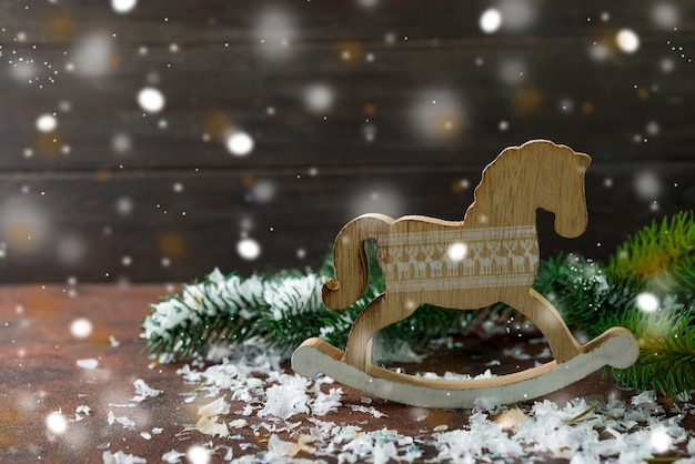 Cheval à bascule en bois jouet comme décorations du nouvel an avec neige et fer arbre Photo Premium
