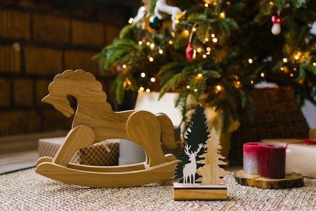 Un cheval à bascule en bois pour enfants se tient à côté de cadeaux de noël sous un sapin de noël avec des lumières Photo Premium