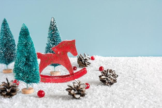 Cheval Jouet Rétro De Noël Avec Des Sapins, Des Baies Rouges Et Des Pommes De Pin Sur Une Table En Bois Recouverte De Neige Photo Premium