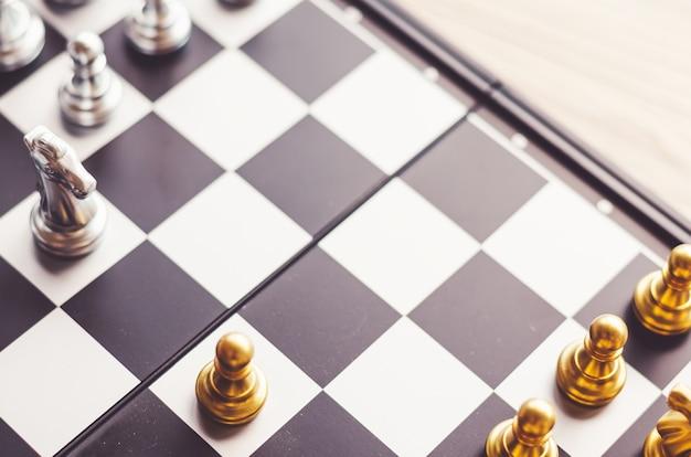 Chevalier D'argent Et D'or Sur L'échiquier. Les Chevaliers D'échecs Tête à Tête. Concept D'entreprise Photo Premium
