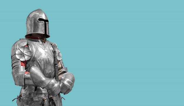 Chevalier médiéval en armure de métal brillant sur fond bleu. Photo Premium