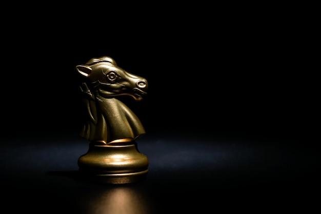 Chevalier d'or aux échecs sur fond noir Photo Premium