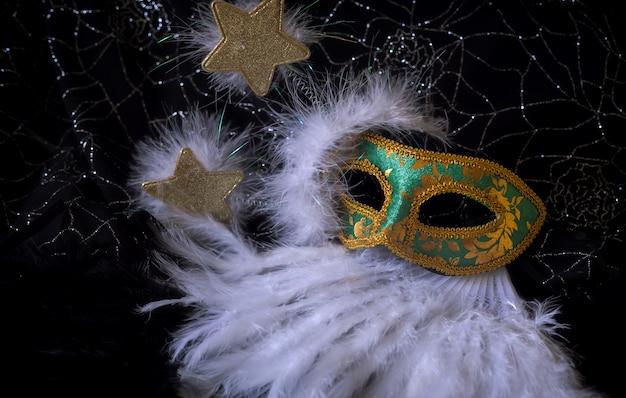 Chic masque vert et doré avec étoiles dorées et fond de plumes blanches pour le carnaval Photo Premium