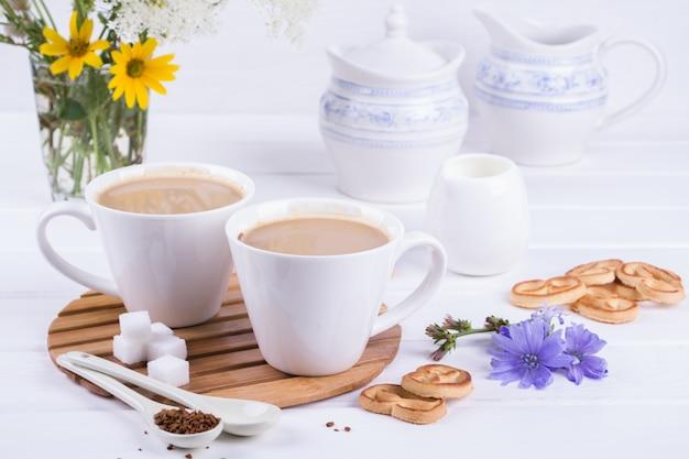 Chicorée De Plantes Médicinales, Régime Alimentaire Chicorée Dans Une Tasse De Lait Pour Le Petit Déjeuner Sur Un Tableau Blanc. Photo Premium