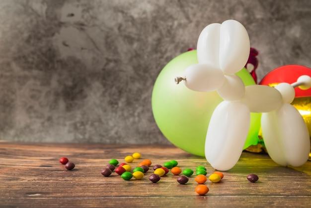 Chien blanc fait avec ballon et bonbons colorés sur table en bois Photo gratuit