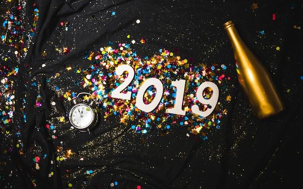 Chiffre décoratif brillant 2019 avec bouteille dorée Photo gratuit