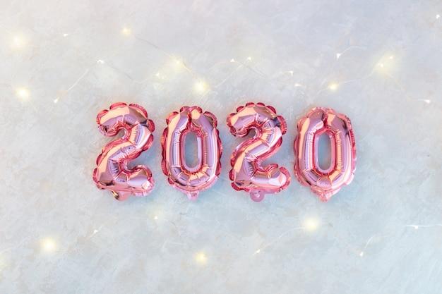 Chiffres roses 2020 sur du béton blanc, une guirlande d'étoiles scintillantes de lumières colorées. Photo Premium