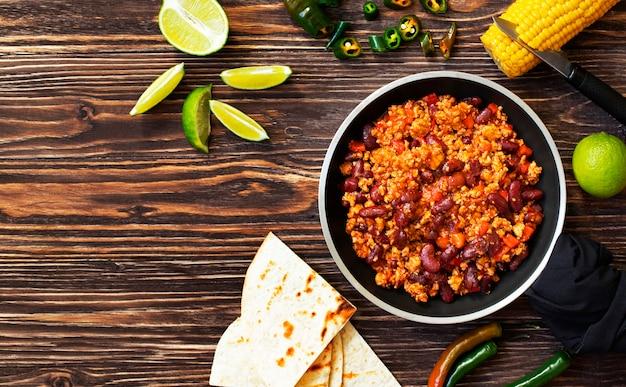 Chili con carne mexicain traditionnel servi sur une table en bois rustique dans une poêle avec maïs, pain mexicain à la tortilla, citron vert et jalapeño. vue de dessus. Photo Premium