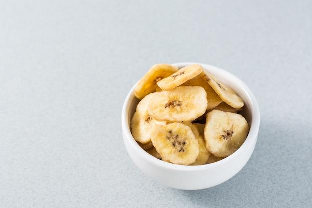 Chips De Banane Au Four Dans Un Bol Blanc Sur La Table. Fast Food. Copier L'espace Photo Premium